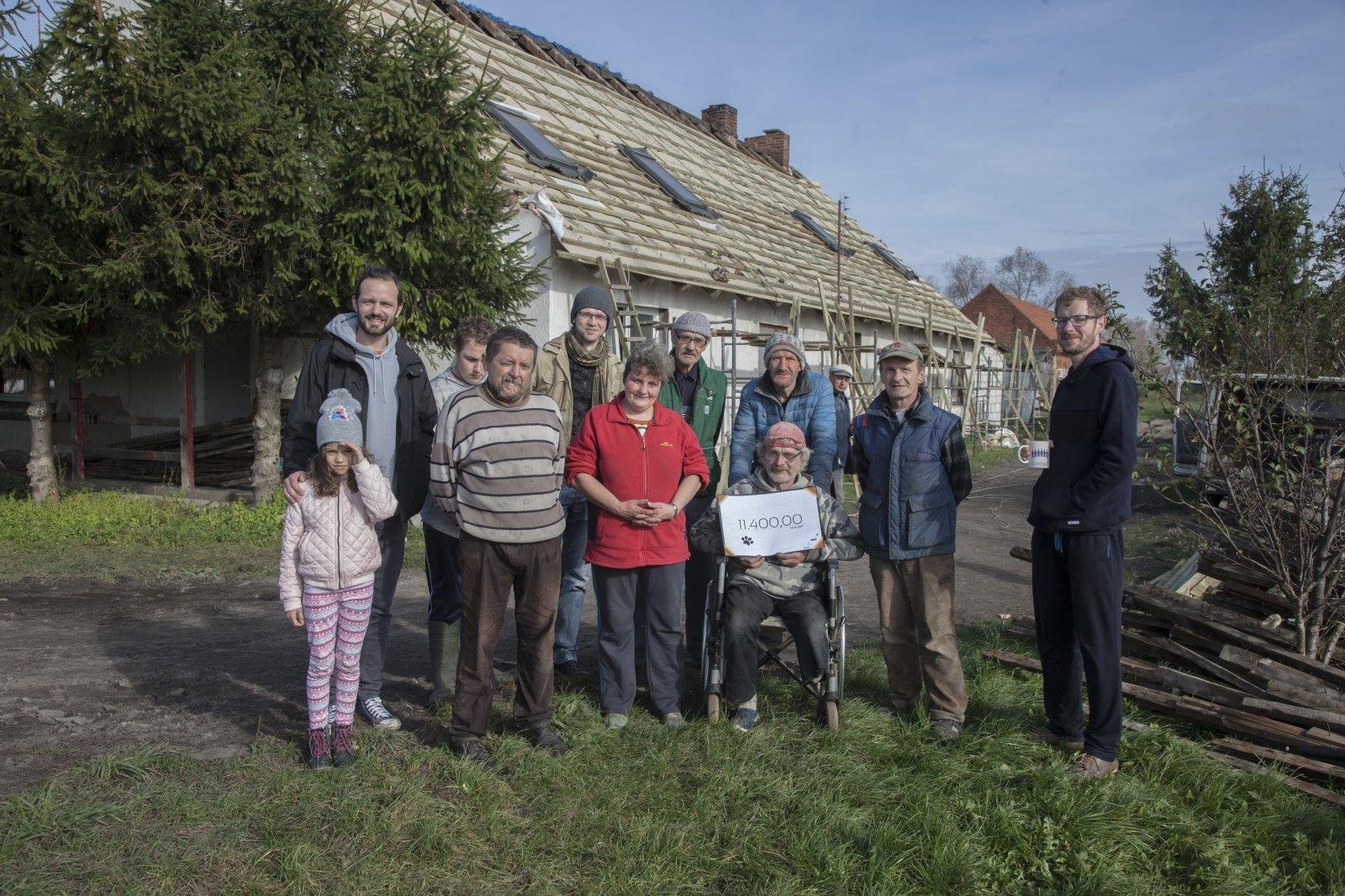 Zdjęcie okolicznościowe przekazania czeku z funduszami - w tle dach, którego budowę współfinansujecie.